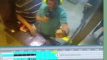 guy points gun at buddies head for a picture